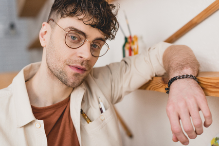 selective focus of handsome artist  in eyeglasses leaning on wooden shelve and looking at camera