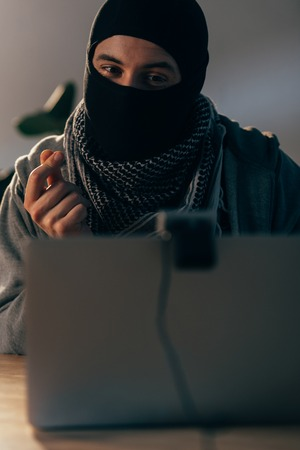 Happy terrorist in mask looking at webcam and showing money gesture