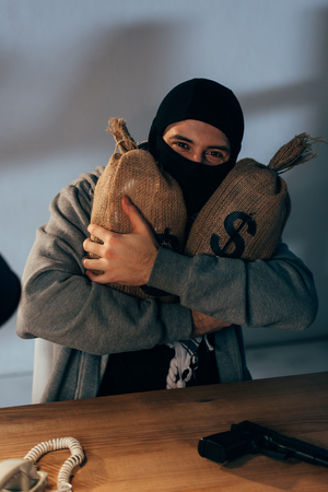 Happy terrorist in mask embracing money bags with dollar signs