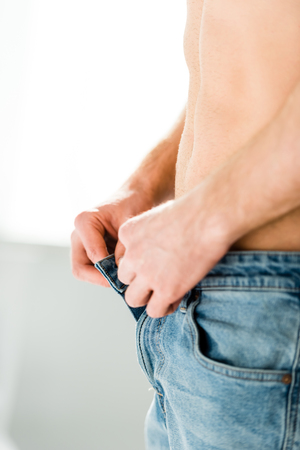 cropped view of man with bare torso taking off blue jeans and standing on white background