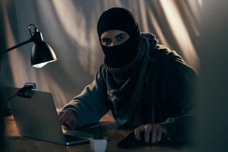 Terrorist in mask with gun using laptop in dark room