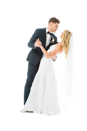 young groom in elegant suit dancing with happy bride isolated on white Stock Photo