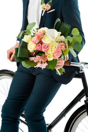 cropped view of groom standing near bike with beautiful wedding bouquet isolated on white Stock Photo
