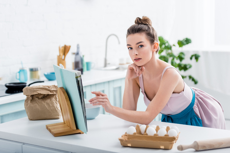 attractive girl touching cookbook and looking at camera with bakery ingredients around