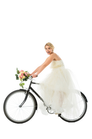 beautiful groom riding bicycle in wedding dress while holding wedding bouquet isolated on white
