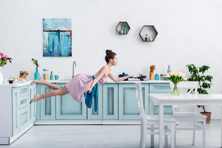 beautiful barefoot girl in elegant dress and apron flying in air with pan in kitchen Standard-Bild