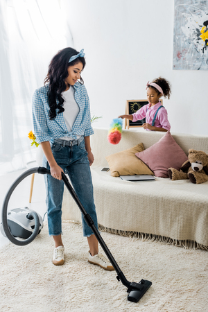 Attractive African American Woman Cleaning Carpet With Vacuum