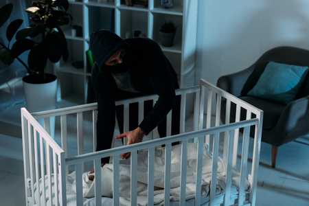 Criminal in mask looking away while kidnapping child from crib