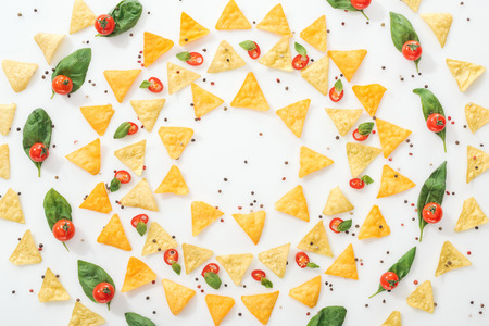 flat lay with tasty nachos, spices and sliced chili peppers with basil and whole cherry tomatoes Stock Photo