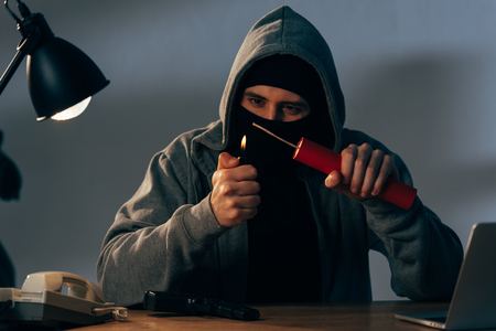 Terrorist in mask and hoodie igniting dynamite in room Stock Photo