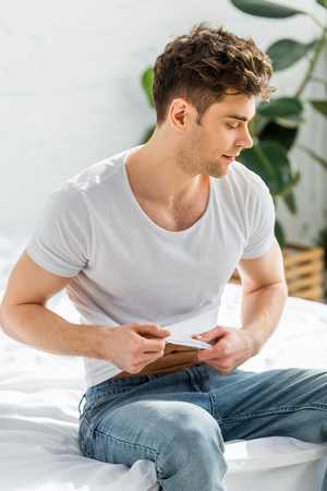 handsome man in jeans sitting on bed and taking off t-shirt in bedroom Stock Photo