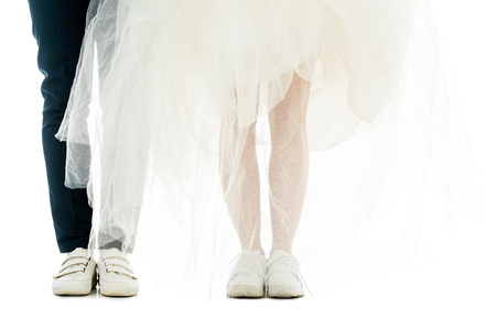 partial view of groom and bride in white sneakers isolated on white