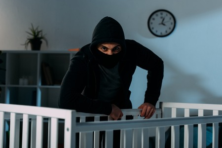 Angry kidnapper in black mask standing near crib and looking at camera Stock Photo