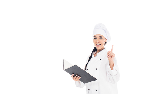 Amazed chef in uniform holding black book and showing idea gesture isolated on white