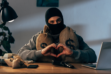 Terrorist in mask with money bags showing heart sign Stock Photo