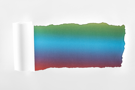 ripped white paper with rolled edge on multicolored background Imagens