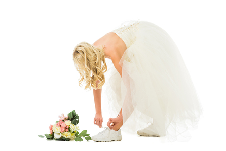 beautiful bride in wedding dress tying shoelaces on sneakers isolated on white