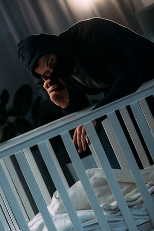 Kidnapper in mask talking on smartphone while standing near crib