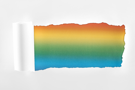 ripped textured white paper with rolled edge on multicolored background