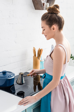 young elegant smiling woman preparing coffee in cezve on oven