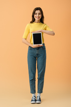 Full length view of smiling girl in jeans holding digital tablet with blank screen on orange background