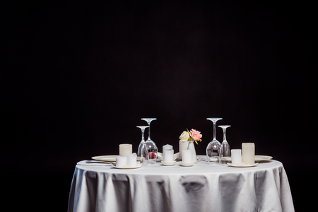 table with white tablecloth, tableware and candles isolated on black Stockfoto