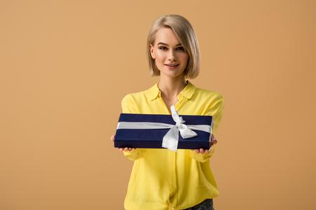 Bella giovane donna bionda che mostra scatola regalo con nastro isolato su beige