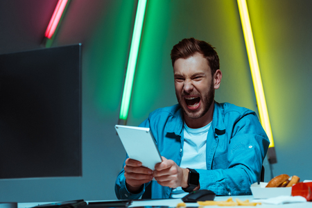 handsome and angry man holding computer keyboard and screaming Stock Photo