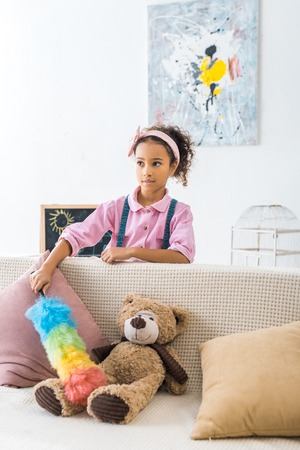 cute african american child dusting sofa with pillows and teddy bear