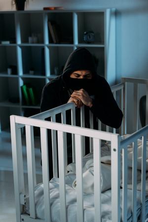 Serious kidnapper in black mask looking in crib in dark room