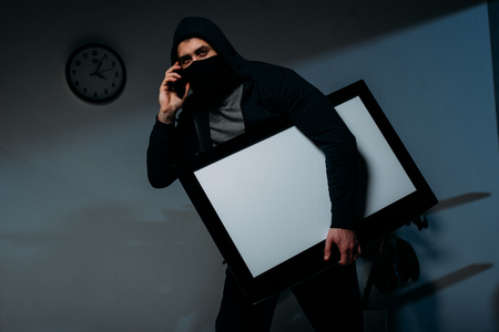 Thief in mask talking on smartphone while stealing flat-screen tv with blank screen Stock Photo