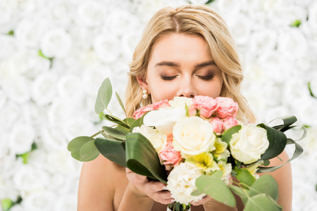 selective focus of young bride with closed eyes enjoying flavor of wedding bouquet on white floral background