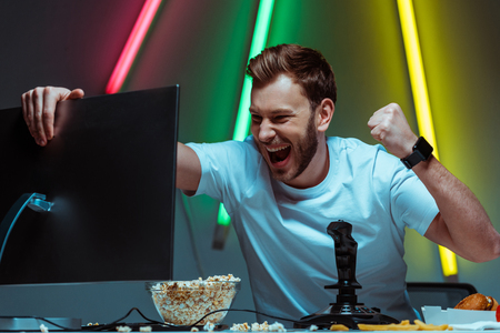 handsome and happy man holding computer monitor and showing yes gesture Banque d'images