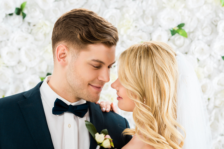 happy young groom and bride standing face to face on white floral background Stock Photo