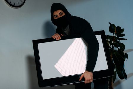 Robber in black mask stealing flat-screen tv with blank screen Stock Photo