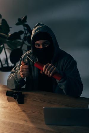 Sly terrorist in mask igniting dynamite in dark room