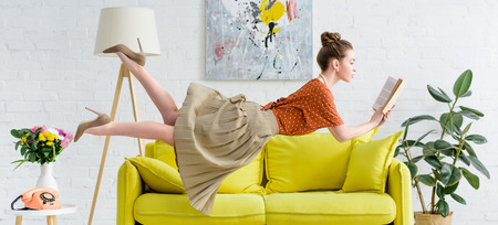 panoramic shot of elegant young woman levitating in air while reading book