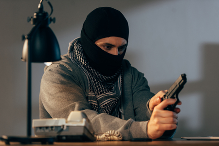 Concentrated criminal in black mask loading gun in room Stock Photo