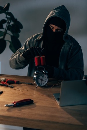 Concentrated terrorist in mask and gloves making bomb in room