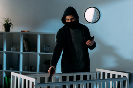 Criminal in mask holding smartphone and aiming gun in crib