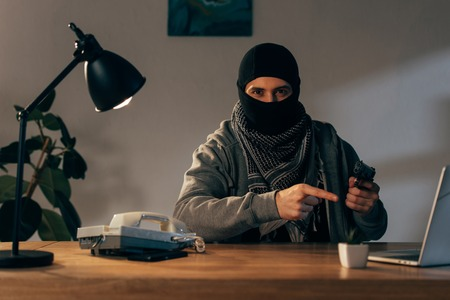 Terrorist in black mask sitting at table and pointing with finger at gun