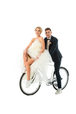 beautiful bride in wedding dress and handsome groom sitting on bicycle isolated on white
