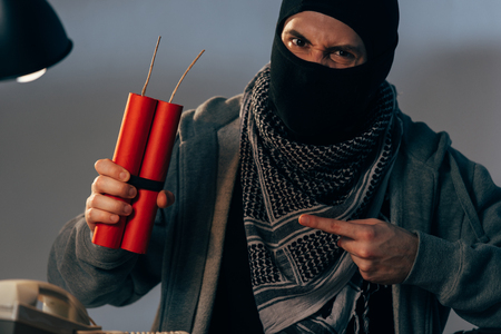 Aggressive terrorist pointing with finger at dynamite and looking at camera Stock Photo