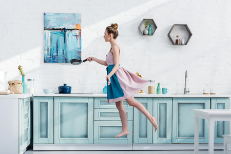 attractive barefoot young woman in apron levitating in kitchen while holding pan