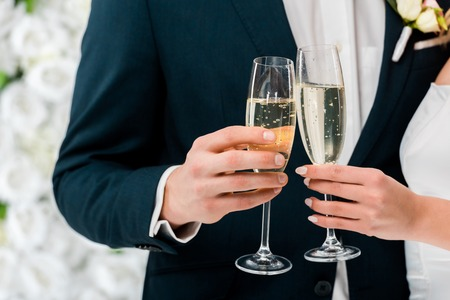 partial view of groom and bride with glasses of champagne on white floral background