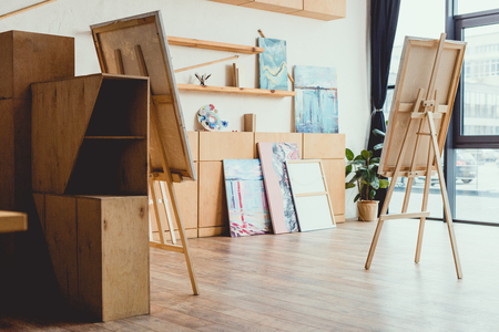 spacious light painting studio with wooden floor, cabinets, shelves, easels and paintings Foto de archivo - 120138294
