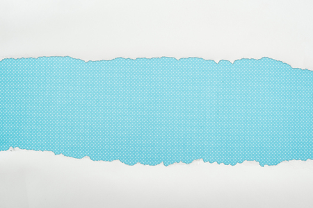 ripped white textured paper with copy space on blue polka dot background