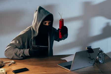 Terrorist in black mask with dynamite aiming gun at webcam
