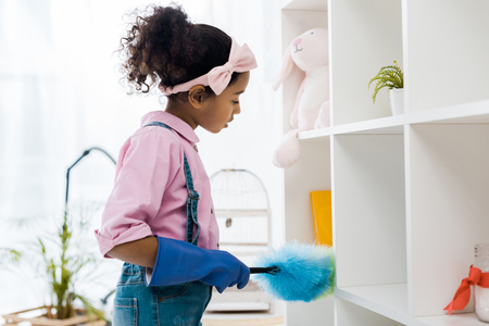 cute african american chid dusting shelving unit