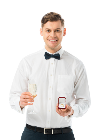 happy groom holding glass of champagne and gift box with wedding ring isolated on white